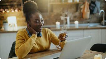 Woman holding a glass of wine while on her laptop.