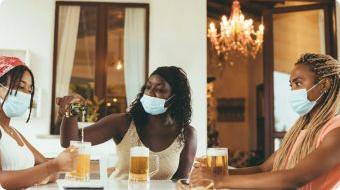 Three people having beer with facemasks on